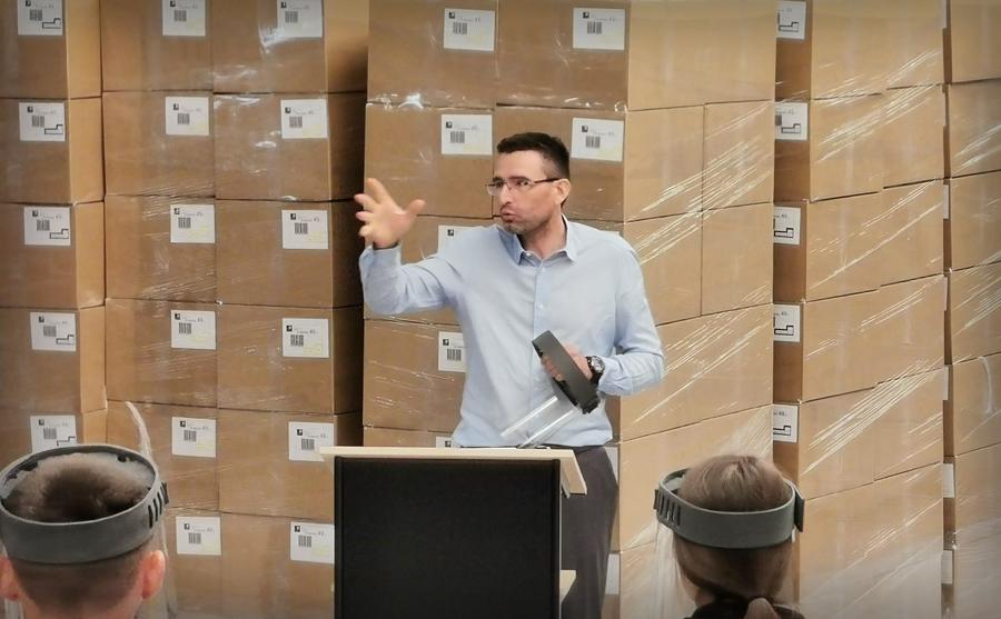 Christophe BECHERT devant des cartons de visières anti-covid